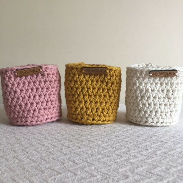 tall crochet pots in light old pink, mustard and off white by Moloneymakes