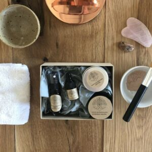 contents of bohobo aromatherapy ritual box includes rose face mist, face oil, pink clay mask, candle and crystal