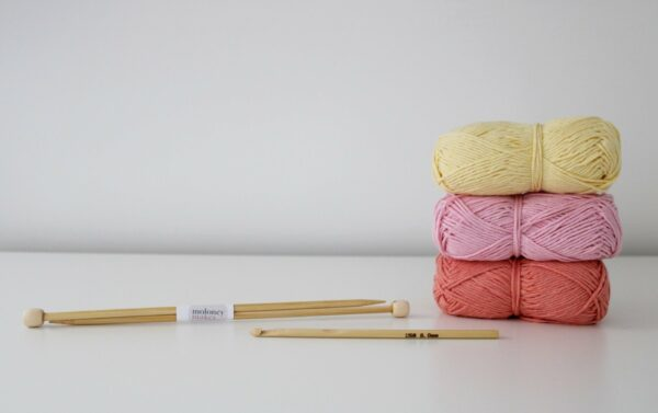 Stack of recycled cotton yarn with bamboo knitting needles and crochet hook