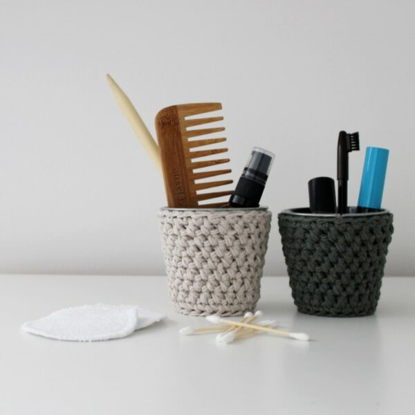 Pair of crochet pots in sand and khaki filled with a comb, oil, make-up and bathroom accessories