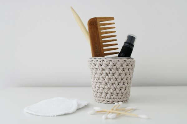 Crochet pot in sand filled with comb and oil with bath accessories