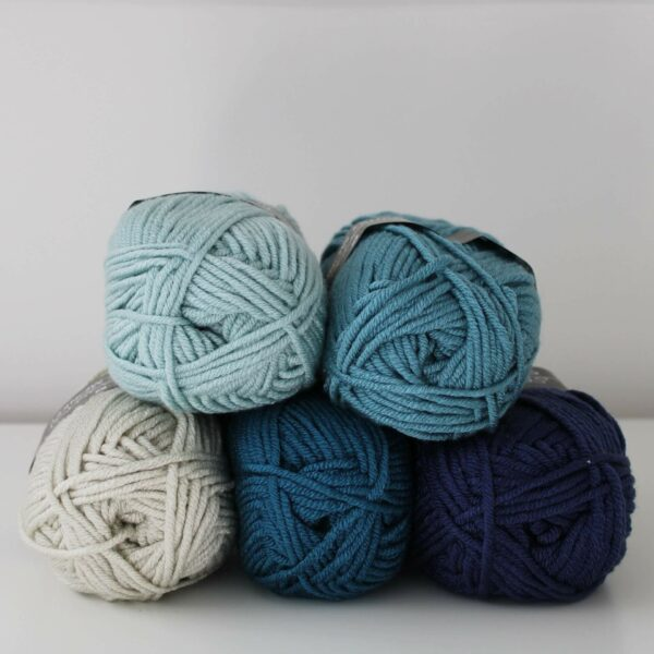 5 balls of scheepjes chunky monkey yarn stacked centrally in mist, blue, stone, petrol and navy