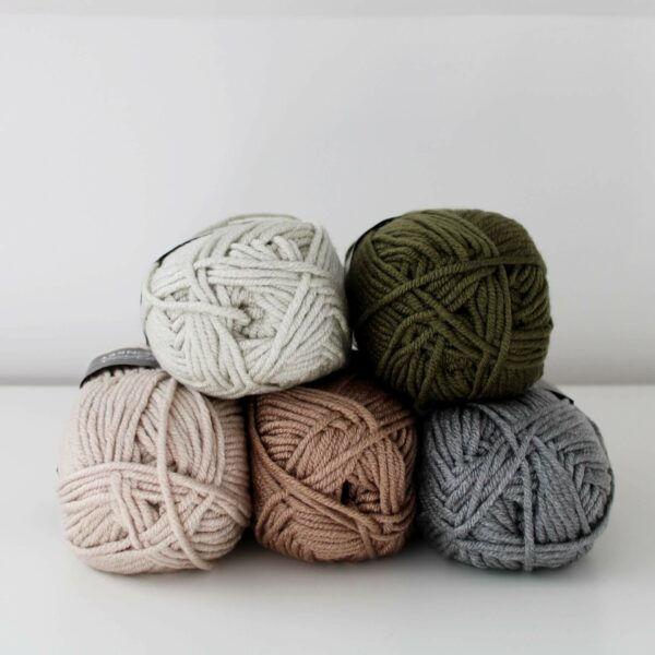 5 balls of scheepjes chunky monkey yarn stacked centrally in stone, khaki, parchment, beige and grey