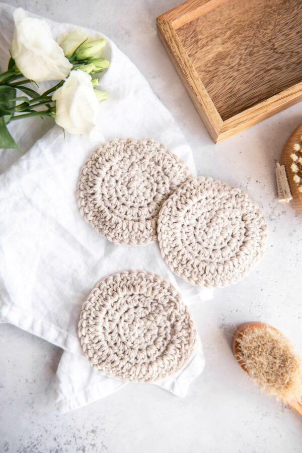 several crochet face scrubbies in sand are pictured in a bathroom set up next to a small body brush