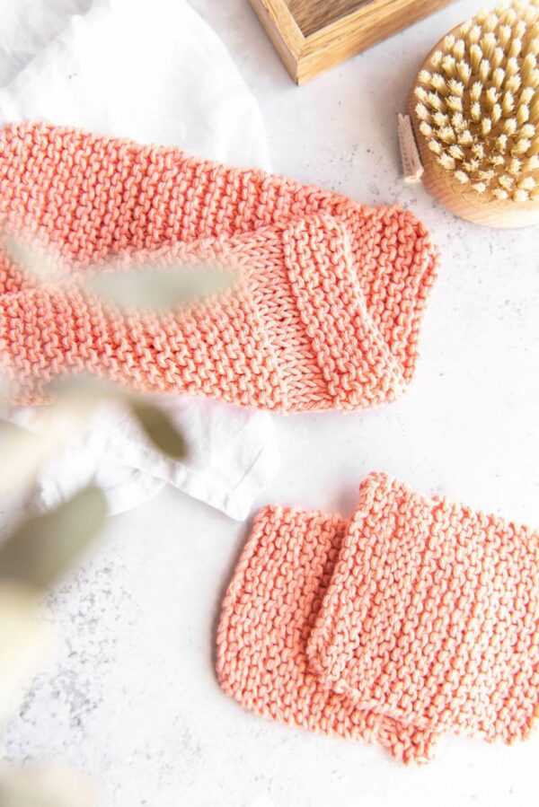 several knitted washcloths in peach are pictured in a bathroom set up next to a small body brush