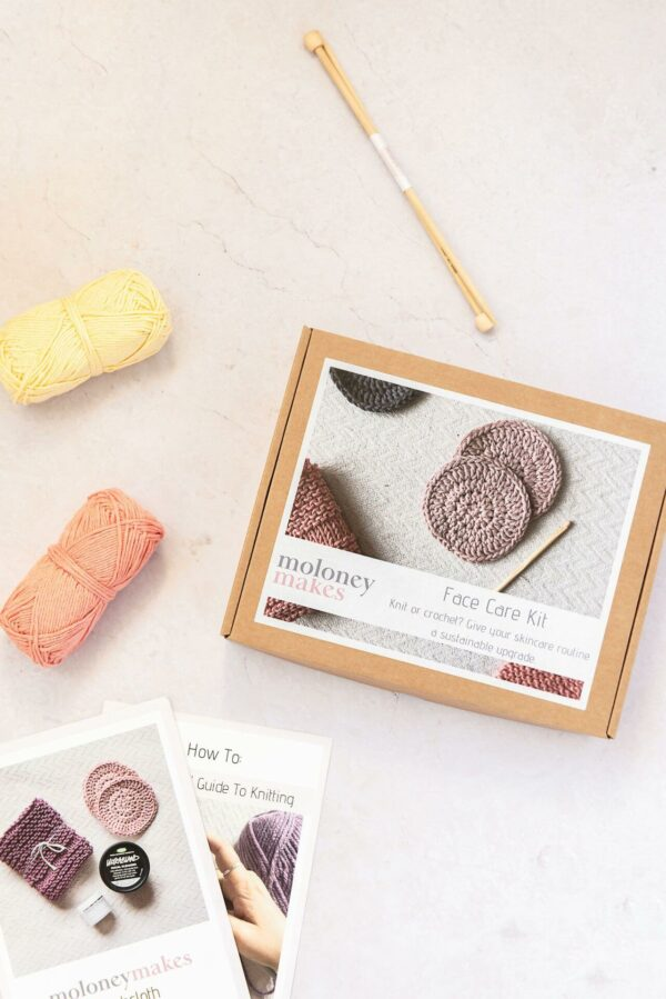 contents of knitted washcloth kit. The box is pictured next to a how to knit guide, a washcloth knitting pattern, 2 balls of recycled cotton yarn in yellow and peach and a set of bamboo knitting needles