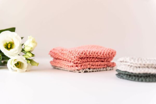 stack of knitted washcloths in peach and sand