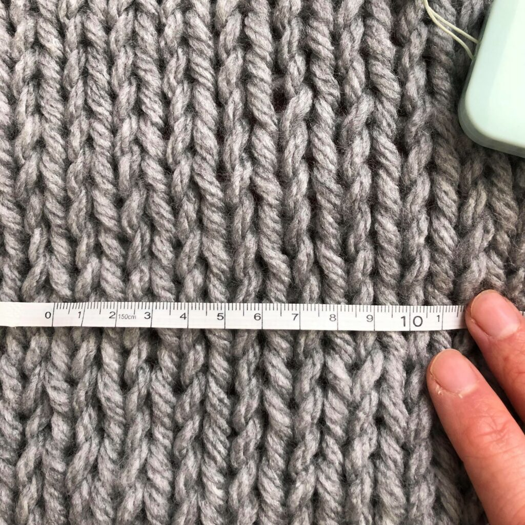 Measuring gauge - a piece of knitting is laid flat, a tape measure is laid horizontally across counting the number of stitches in 10cm