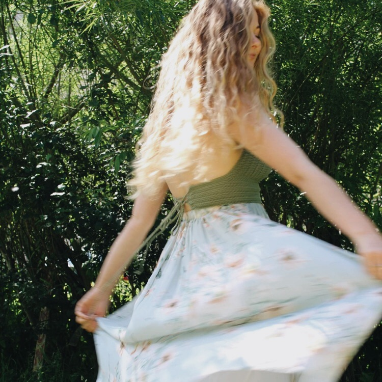 Sophie wears the Isabella crochet bralette in green with a highwaisted chiffon floral print skirt. She's stood outside amongst bushes and trees swishing her skirt
