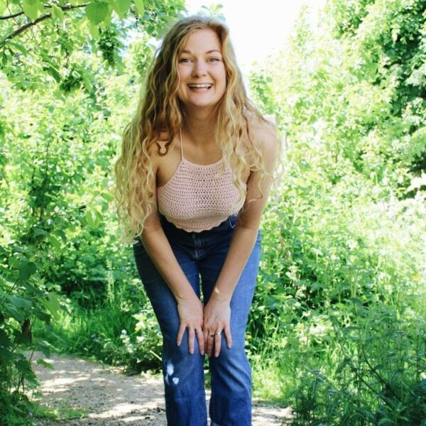 Sophie wears the Pippa crochet crop top in light pink with a pair of blue mom jeans. She's stood outside amongst bushes and trees and crouching down, smiling at the camera