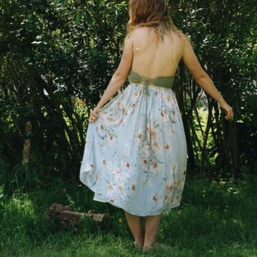 Sophie wears the Isabella crochet bralette in green with a highwaisted chiffon floral print skirt. She's stood outside amongst bushes and trees with her back to the camera looking down over her shoulder swishing her skirt
