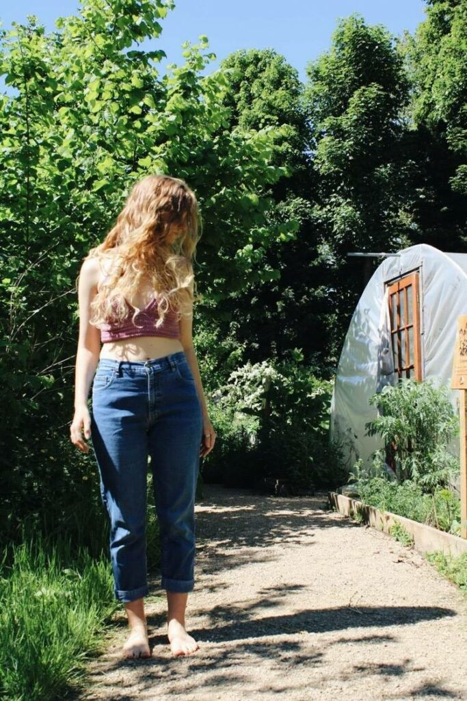 Sophie wears the Isabella crochet bralette in dusky pink with a pair of blue mom jeans. She's stood outside amongst bushes and trees