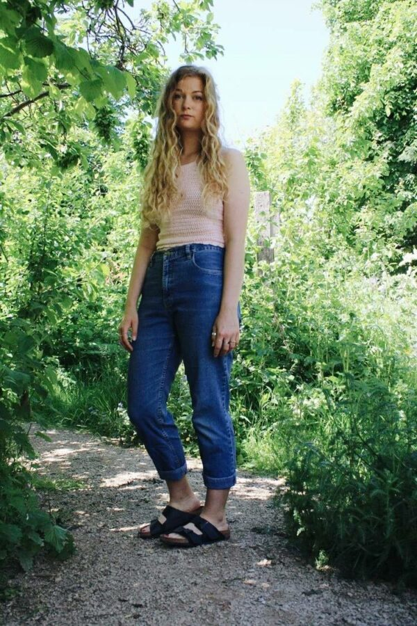 Sophie wears the Pippa crochet tie back top in light pink with a pair of blue mom jeans. She's stood outside amongst bushes and trees and looks moodily at the camera