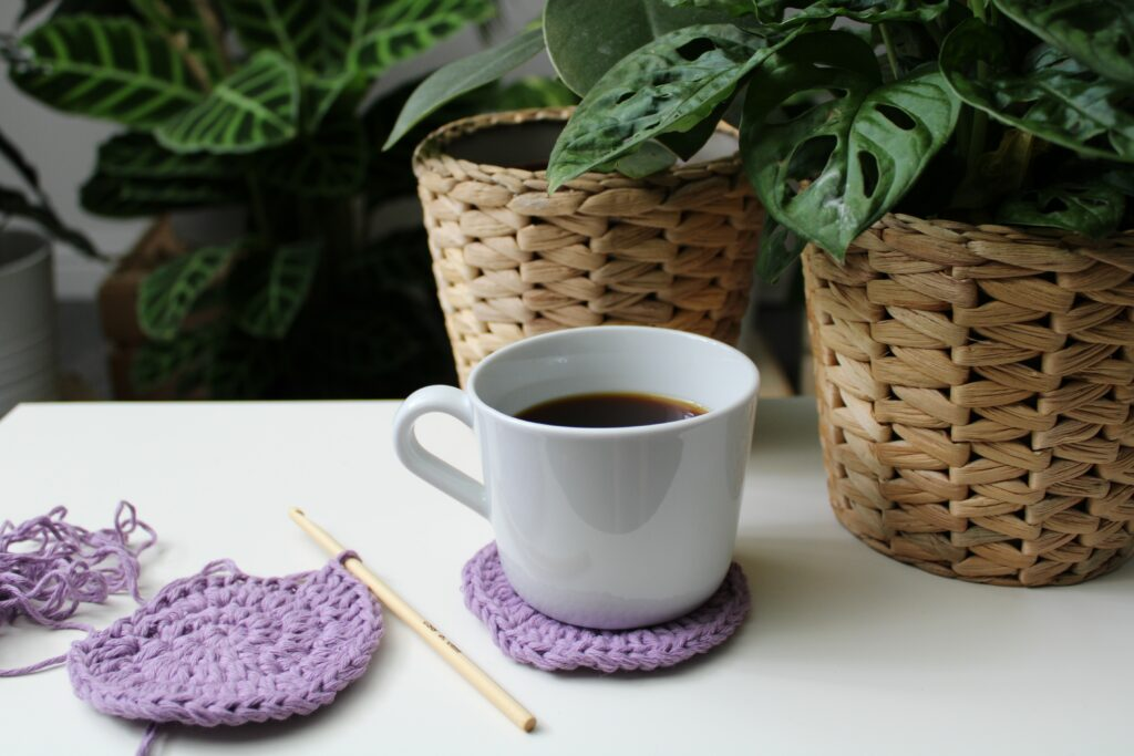 A white coffee cup sits on a lilac crochet coaster made using Hoooked recycled cotton DK next to a half finished coaster