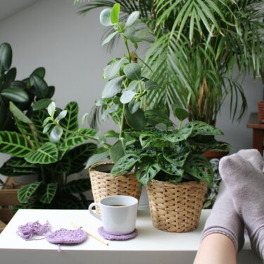 A white coffee cup sits on a lilac crochet coaster made using Hoooked recycled cotton DK next to a half finished coaster. There are a pair of feet resting on the right side of the table - a lovely image of a mindful break in action