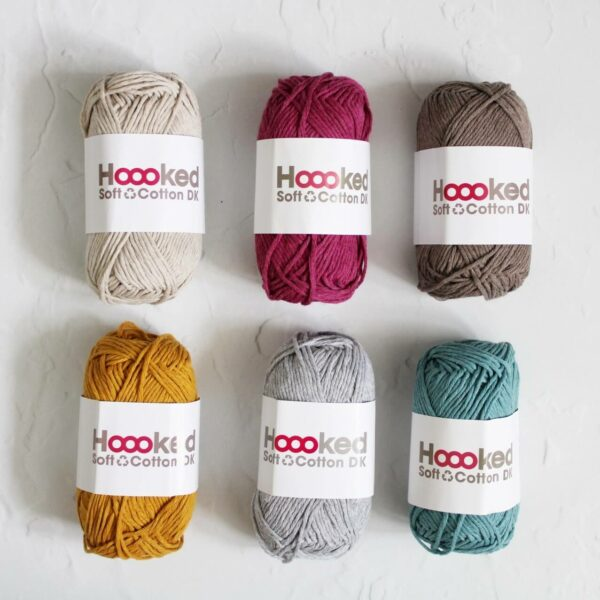 Hoooked Recycled Cotton Yarn Bundle. 6 50g balls of cotton in a variety of shades sits on a white textured background