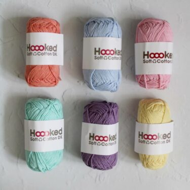 Hoooked Recycled Cotton DK Bundle. 6 50g balls of cotton in a variety of pastel shades sits on a white textured background