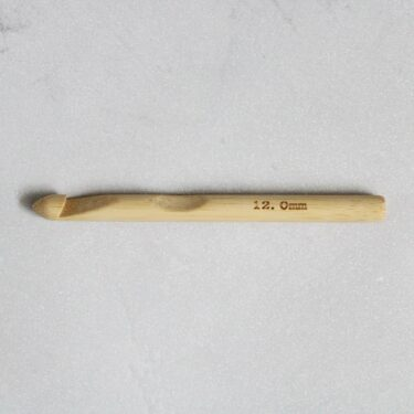 12mm bamboo crochet hook on a grey background