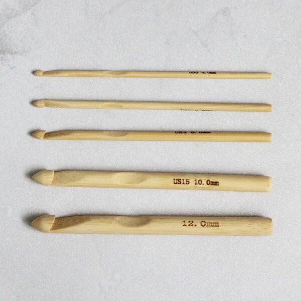 a collection of bamboo crochet hooks on a grey background