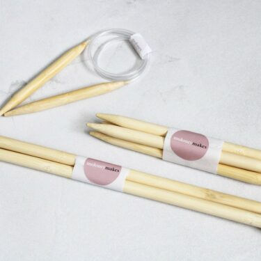 A collection of 12mm Knitting Needles on a grey background