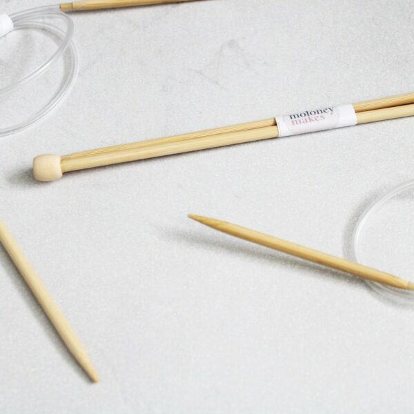 A collection of 5mm Knitting Needles on a grey background