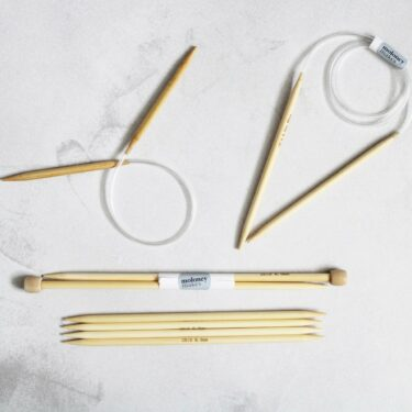 A collection of 6mm Knitting Needles on a grey background