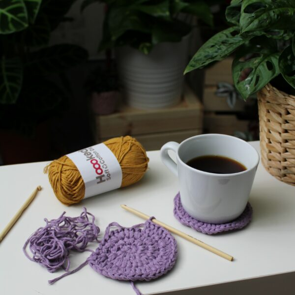 A white coffee cup sits on a lilac crochet coaster made using Hoooked recycled cotton DK next to a half finished coaster and a ball of mustard cotton