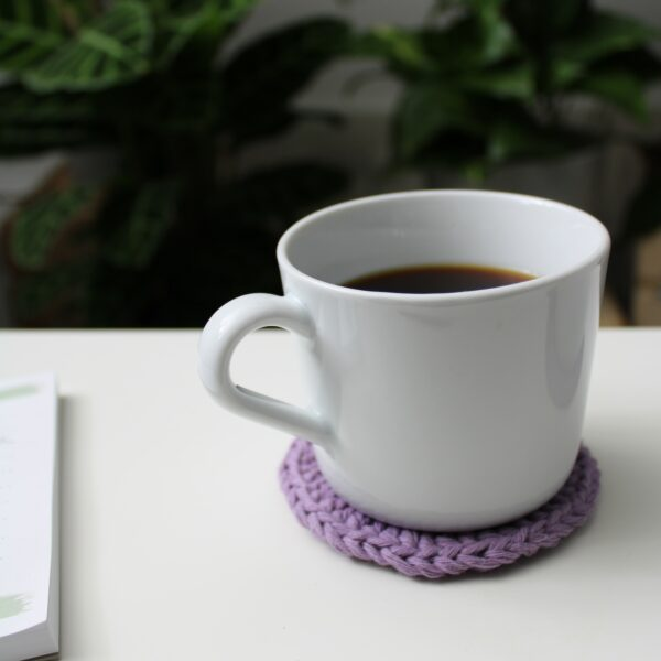 A white coffee cup sits on a lilac crochet coaster made using Hoooked recycled cotton DK