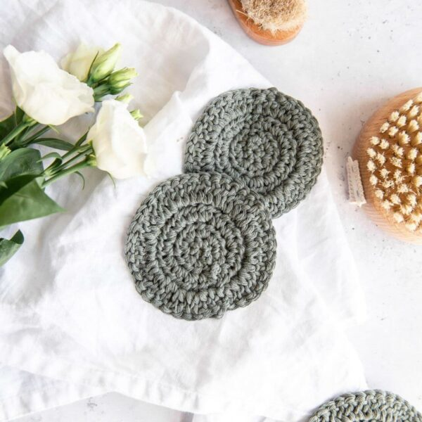 several crochet face scrubbies in khaki are pictured in a bathroom set up next to a small body brush