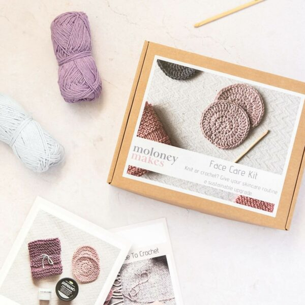 contents of crochet face scrubbie kit. The box is pictured next to a how to crochet guide, a face scrubbie crochet pattern, 2 balls of recycled cotton yarn in light blue and lilac and a bamboo crochet hook