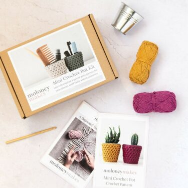 contents of mini crochet pot kit. The box is pictured next to a how to crochet guide, a pot cover crochet pattern, 2 balls of recycled cotton yarn in mustard and plum, a metal pot and a bamboo crochet hook