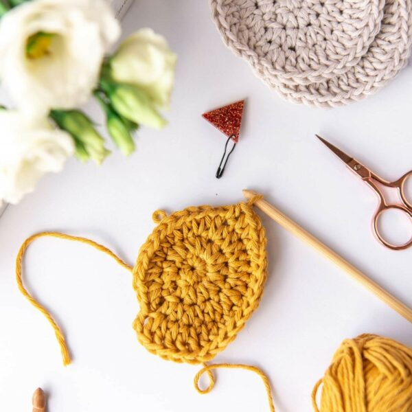 crochet face scrubbie work in progress in mustard cotton yarn sits on top of 91 magazine surrounded by crochet and craft tools