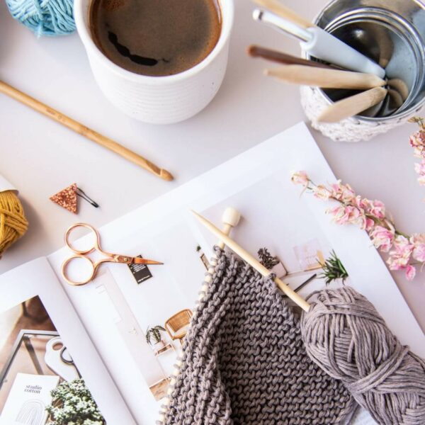 knitted washcloth work in progress in taupe sits on top of 91 magazine surrounded by coffee and craft tools