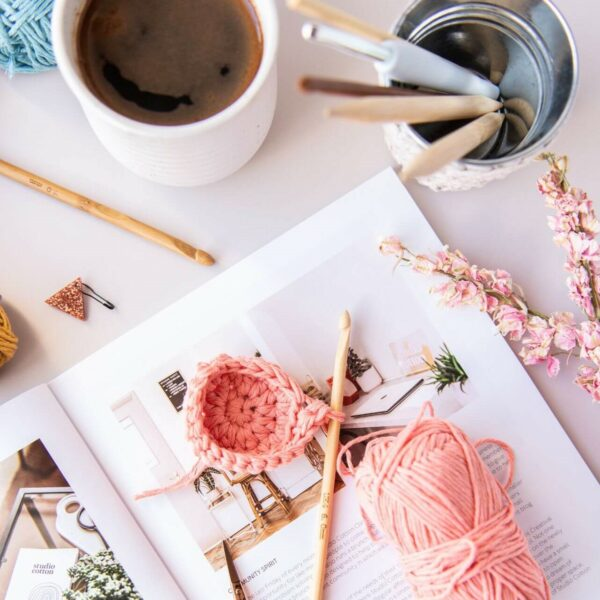 mini crochet pot work in progress in peach sits on top of 91 magazine surrounded by coffee and craft tools