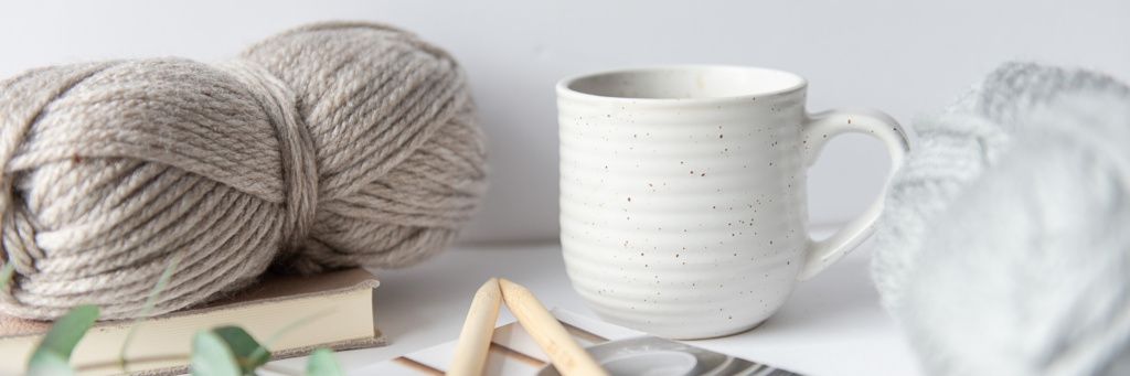 A coffee cup sits alongside balls of yarn in oatmeal and grey and a pair of bamboo knitting needles on top of a copy of Koel magazine