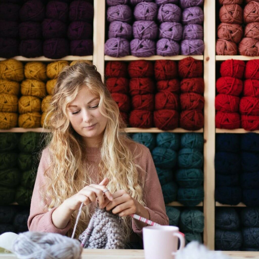 Sophie Moloney, owner of Moloneymakes, sits at her desk in front of a colourful wall of yarn. She is knitting, looking down as she works with a slight smile on her face