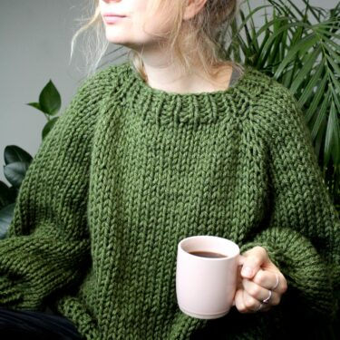Sophie wears your new favourite jumper in fern green. She is holding a pink mug containing black coffee and is looking in the distance
