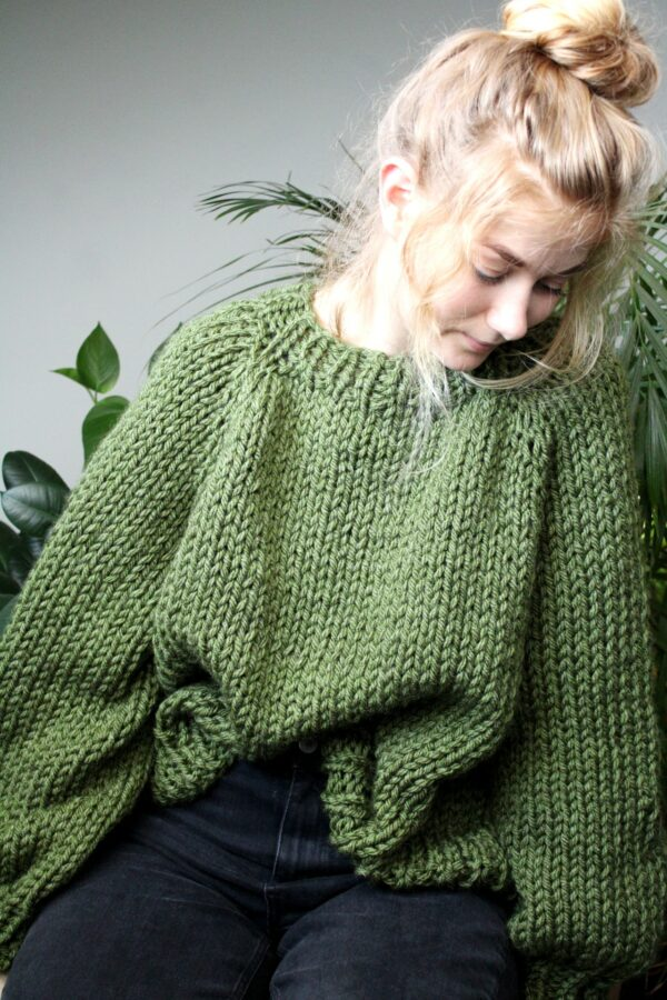 Sophie wears your new favourite jumper in fern green. She is smiling slightly looking down