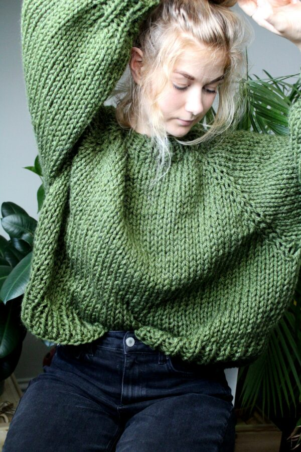Sophie wears your new favourite jumper in fern green. She has her arms raised to show off the jumper torso, looking down at the floor