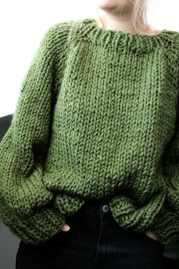 Sophie wears your new favourite jumper in fern green. It is tucked in at the front and she has her hand in her pockets