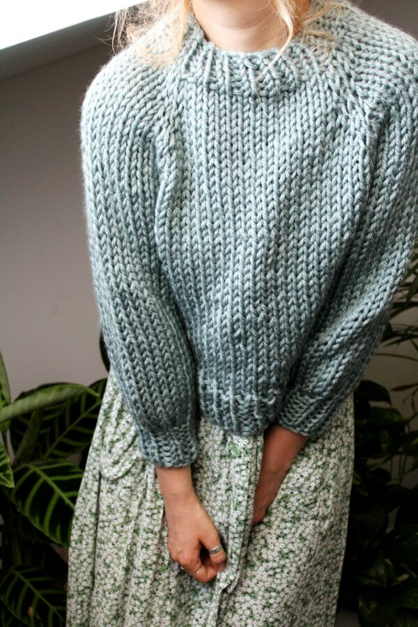 Sophie wears your new favourite jumper in glacier. It's layered over a floral print midi dress. Her face is out of shot and her hands together at her lap