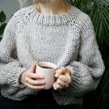 Sophie wears your new favourite jumper made from the jumper knitting kit in oatmeal. She is holding a pink mug containing black coffee and is looking into the distance