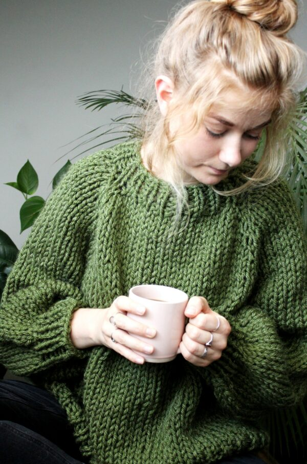 Sophie wears your new favourite jumper in fern green. She is holding a pink mug containing black coffee and is looking down