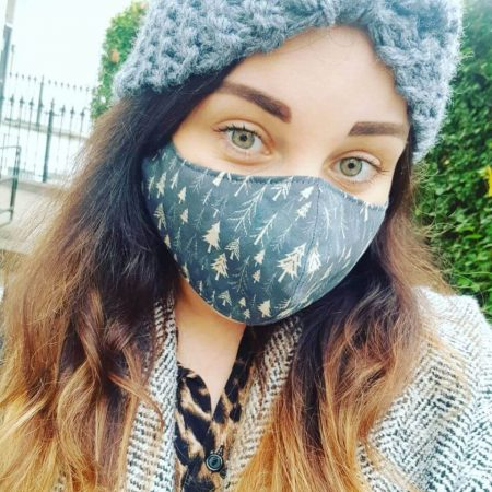 Ali is wearing a daisy turban headband in graphite. She has long brown hair and is wearing a coordinating facemask