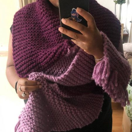 rachel is wearing her oversized tassel scarf knitted using our super chunky vegan yarn in bramble and redcurrant
