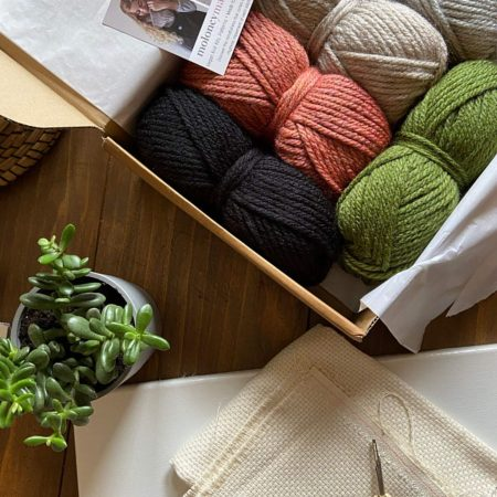 Black, rust, oatmeal, green yarn in a box with punch needle supplies